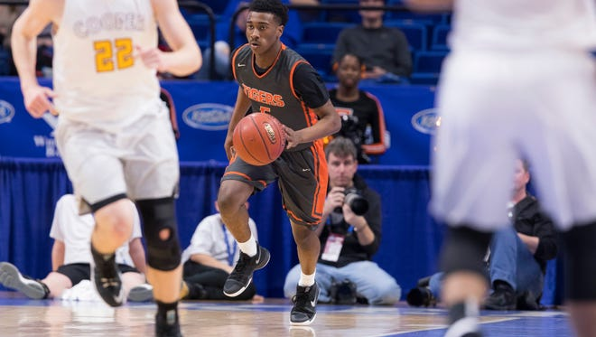 Fern Creek's Anthony Wales (5) brings the ball up the court during the quarterfinal game of the KHSAA Boys Sweet 16 between the Fern Creek Tigers and the Cooper Jaguars.