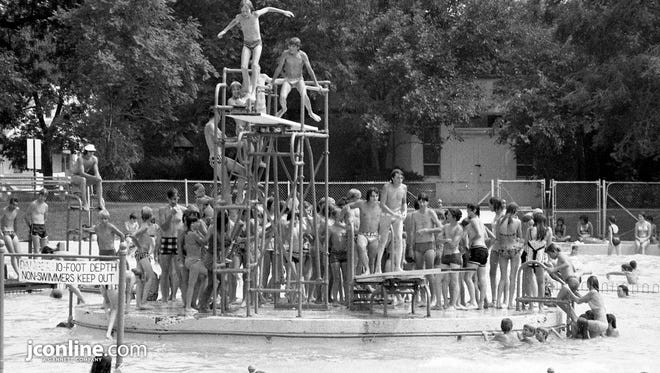 Youngsters in jam-packed Columibna Pool virtually spill over the sides of the concrete island where the diving boards provide an exit into the cool water. City pools were popular spots in the 90-degree heat. Photo taken July 9, 1974.