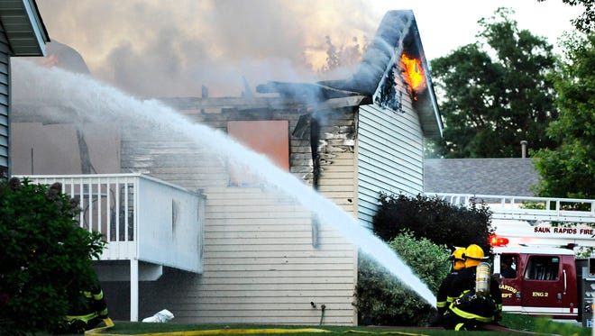 Firefighters from area departments battle the flames after a small plane crashed into a home at 731 Garden Place in Sauk Raids, Minn., Friday, June 20.