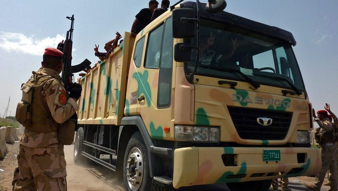 Military trucks transport Iraqi volunteers to Muthanna base in central Baghdad on June 13, 2014.