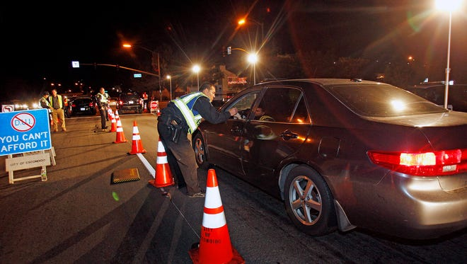 """In this Dec. 16, 2011, photo, police officers check drivers at a sobriety checkpoint in Escondido, Calif. At """"No Refusal"""" checkpoints, on-call judges can issue a warrant for a blood test from a suspected impaired driver."""