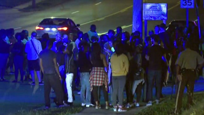 In this framegrab image courtesy of KSDK-TV a crowd gathers near the scene where a police officer was shot in the arm Saturday night Sept. 27, 2014 in Ferguson, Missouri. The officer was shot in the arm and is expected to survive, St. Louis County Police Chief Jon Belmar said.