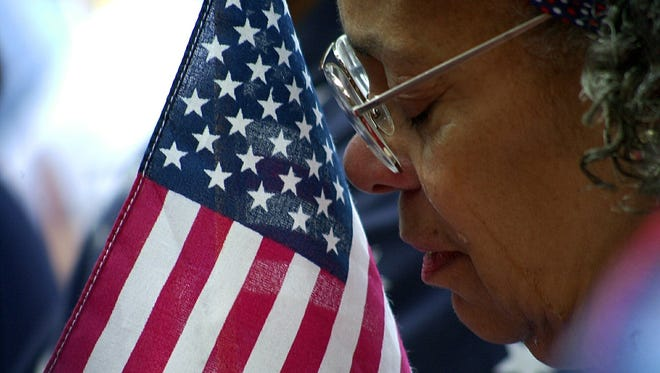 Barbara Quarles of New Rochelle bows her head at a 9/11 remembrance on the steps of New Rochelle City Hall on Sept. 11, 2002.