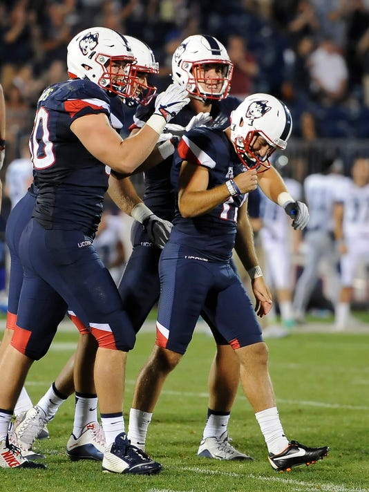 Connecticut's Bobby Puyol (17), right, is congratulated by his teammates after making a field goal during the second half of an NCAA college football game Thursday, Sept. 1, 2016, in East Hartford, Conn. (AP Photo/Jessica Hill)