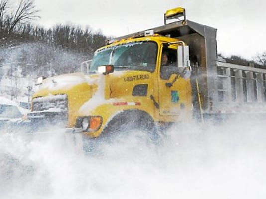 A snow plow is barely visible as deep snow is pushed to the side of Benjamin Franklin Highway in Douglass (Berks) Township.