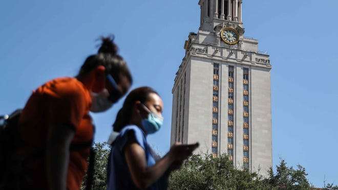 People wear masks as they pass in front of the University of Texas Tower on Friday. UT classes will start Wednesday. Most will be online, but some will be in-person and some will be a hybrid of online and in-person.
