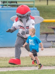 Kids get to run the bases with the help of Mo Skeeter during Tueday's game against the Kalamazoo Growlers.