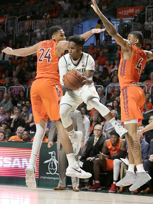 Miami's Chris Lykes (2) finds a gap between the Virginia Tech defense during an NCAA college basketball game Saturday, March 3, 2018 in Coral Gables, Fla.(Andrew Uloza/Miami Herald via AP)