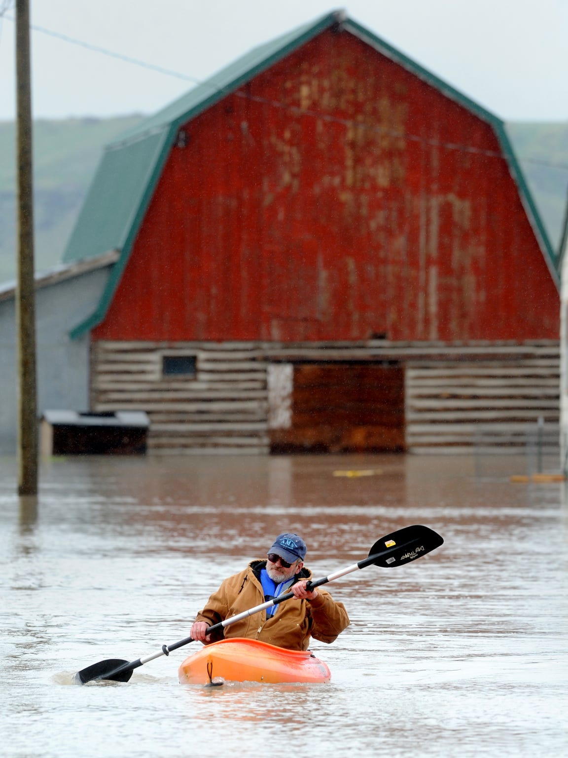 A resident of Sun River paddles a kayak up his driveway during the flooding of the Sun River 2011.