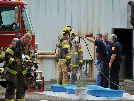 "A firefighter is sprayed down with water after leaving the Retriev Technologies building Wednesday afternoon, July 30, 2014, in Walnut Township. Firefighters responded a lithium battery fire at the plant. ""We call it 'gross decon,'"" Millersport Fire Chief Bob Price said. ""We're just washing the guys off. Anybody that was inside and in contact with the smoke or with the fire itself, we're just bringing them out and washing them off."""
