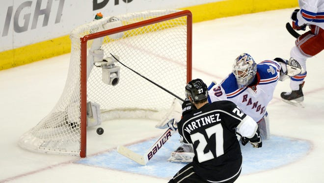 Los Angeles Kings defenseman Alec Martinez (27) scores the game-winning goal past New York Rangers goalie Henrik Lundqvist (30) during the second overtime period in game five of the 2014 Stanley Cup Final at Staples Center.