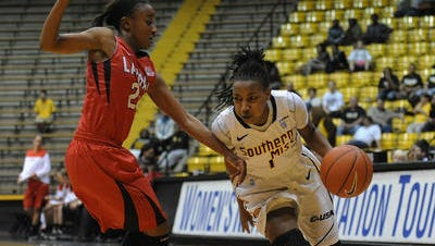 Southern Miss guard Jamierra Faulkner (1) pushes past Lamar guard JaMeisha Edwards (20) Thursday during the first round WNIT game at Reed Green Coliseum.