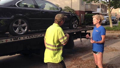 Tina Sellers discusses the damage to her car with a tow truck driver after floodwaters disabled it in downtown Pensacola. She called for a truck Wednesday and had to wait until Thursday evening.