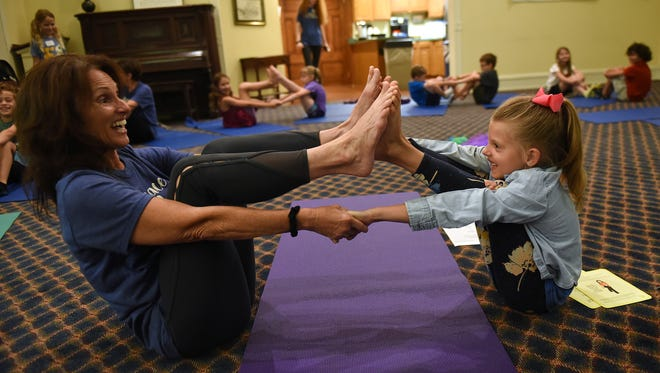 Yoga teacher Karen Scott and Emma Dondurand, 7, do boat pose together during a yoga session at Peace Village Camp at United Church of Granville. Scott teaches youth yoga at Breathe @ Granville Yoga.