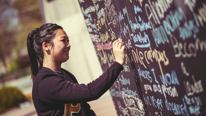 "A student writes a message on a chalk wall as part of Purdue Day of Giving 2015. The day of giving was part of the silent phase of Purdue's $2 billion ""Ever True"" Campaign"