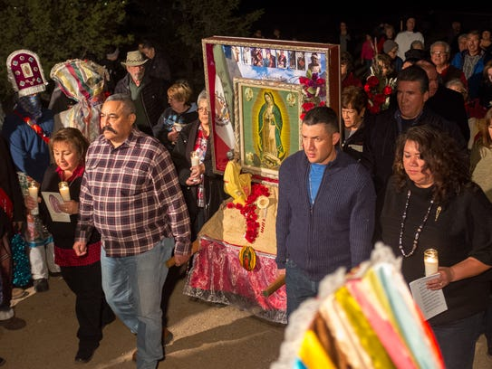 A candlelight procession from La Capilla prepares to