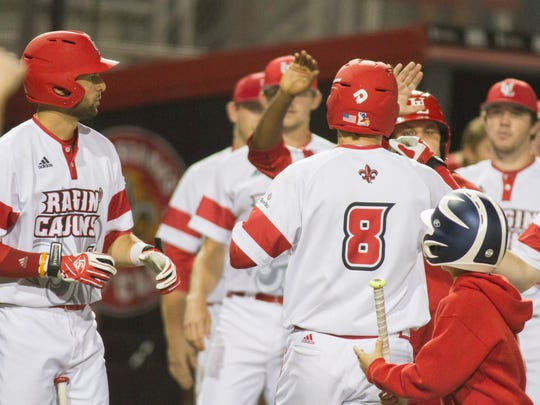 UL's Derek Herrington (8) is congratulated by teammates