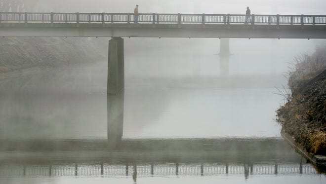 Two people walk the Princess Street bridge across the Codorus Creek in York amid a dense fog advisory in January 2014. The bridge is one of 95 bridges York County owns.