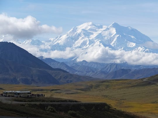 Sightseeing buses and tourists are seen at a pullout popular for taking in views of North America's tallest peak, Denali, in Denali National Park and Preserve, Alaska.