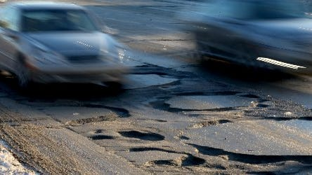 Cars navigate potholes in Southfield.
