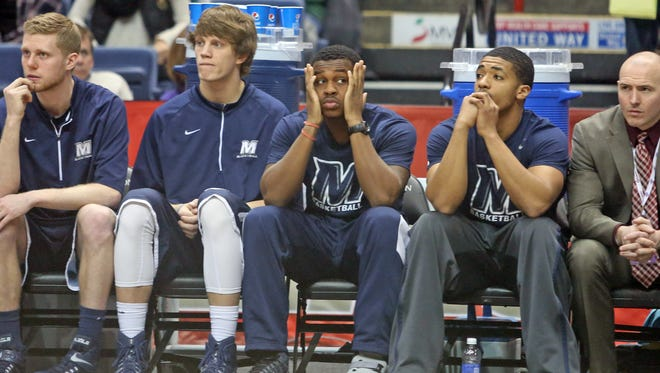 Josh James of Monmouth, center, a Stepinac High School graduate, sits on the bench with a toe injury during Iona's 95-77 win over Monmouth in a MAAC Championship semifinal game at the Times Union Center in Albany March 8, 2015.