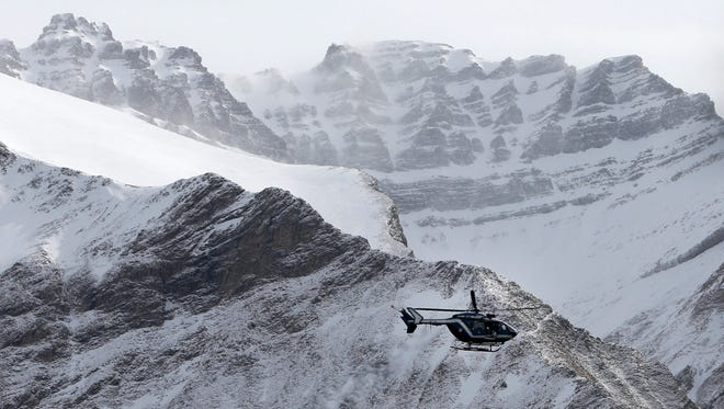 A helicopter carries search-and-rescue workers to the crash site of the Germanwings Airbus A320 that crashed in the French Alps, above the town of Seyne-les-Alpes, southeastern France, March 25, 2015.