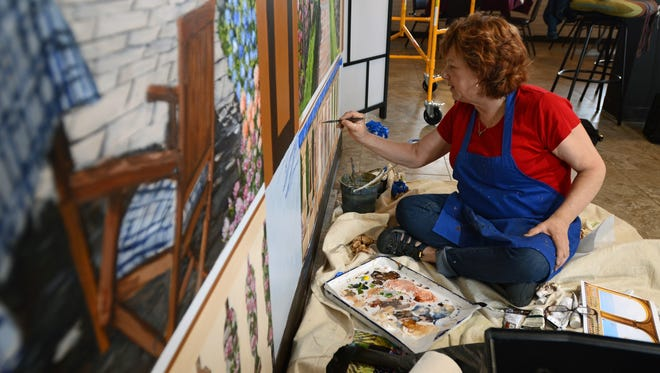 Artist Jenny Walker works on a water and Italian countryside inspired mural Monday, June 13, at Great Lakes Italian restaurant in Fort Gratiot Township.
