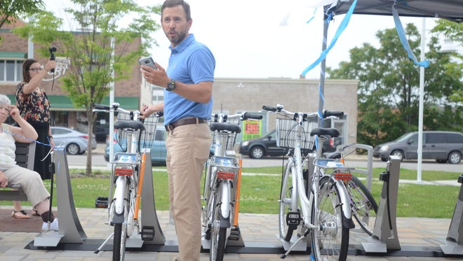 Dave McElroy, assistant general manager and finance director for Blue Water Area Transit, which spearheaded Port Huron's new bike-sharing program, demonstrates how the Zagster app can be used to unlock a bike from a docking station outside BWAT's bus hub on Wednesday, July 12, 2017.