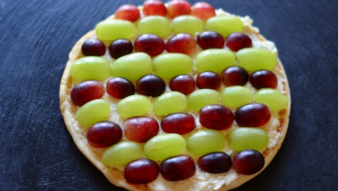 Transform extra grapes into a pizza with this easy snack or dessert. Pita is covered in sweetened cream cheese and then topped with grapes. Kids will love it.