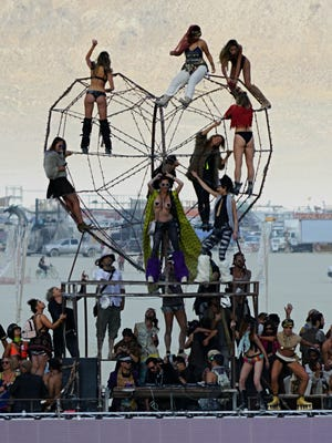 Hundreds of dancers congregate around a mobile DJ sound bus in the middle of the desert at Burning Man as the sun rises on Tuesday morning.