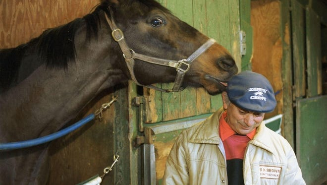 Zippy Chippy playfully (or not) takes a nip at the cap of trainer Felix Monserrate before a race in 2000 in New Jersey. Mr. Monserrate died this week. He was 72.