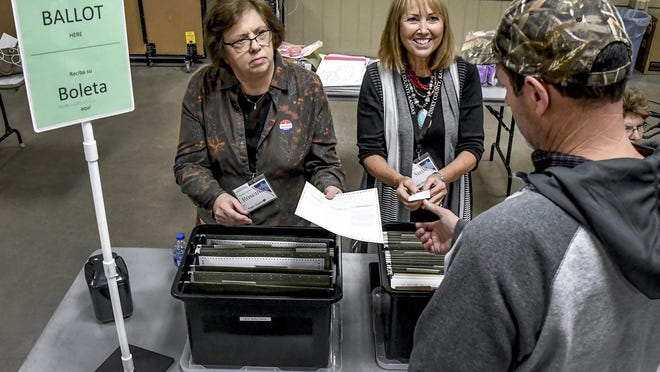 Rosemary Wehkamp, left, hands a paper ballot to a voter in November 2019 as she and fellow election workers Susie Gooden and Marilyn Wadel work one of the tables in the Finney County Fairgrounds 4-H bulding during the general election. Voters had a choice of casting their votes using either a paper or electronic ballot.