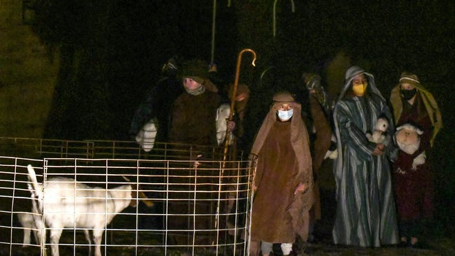 """Masked shepherds, for the COVID-19 pandemic, keep watch over their flocks Saturday in a scene from the First United Methodist Church's annual performance of a """"Living Christmas""""."""