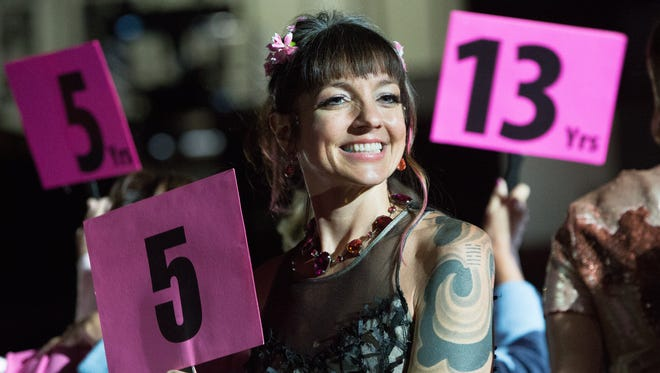 Beth Duncan, one of over 30 cancer survivors to walk the runway at the at the Tough Enough to Wear Pink Fashion Show, holds a card marking the years she has survived cancer as she and the other survivors gather on the runway together at the end of the fashion show, Thursday October 20, 2016 at the Pan American Center.