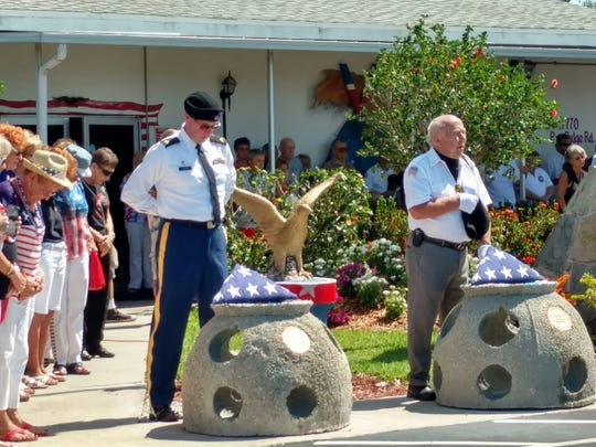 Attendees bow their heads in prayer during a Memorial Day service honoring six men who died during a World War II training flight.