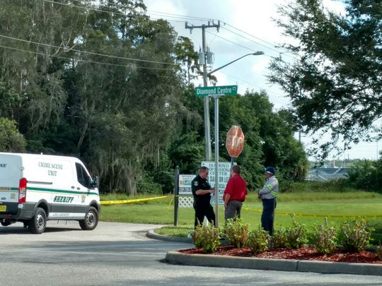 Law enforcement talks with a landscape employee about 100 yards from where a body was found Monday morning. The bleachers at South Fort Myers High School are in the background.