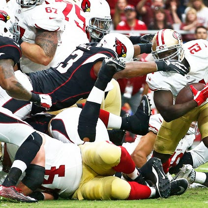 Arizona Cardinals' Calais Campbell drives over the line and stops San Francisco 49ers running back Frank Gore in the first half on Sunday, Sept. 21, 2014, at University of Phoenix in Glendale, Ariz.
