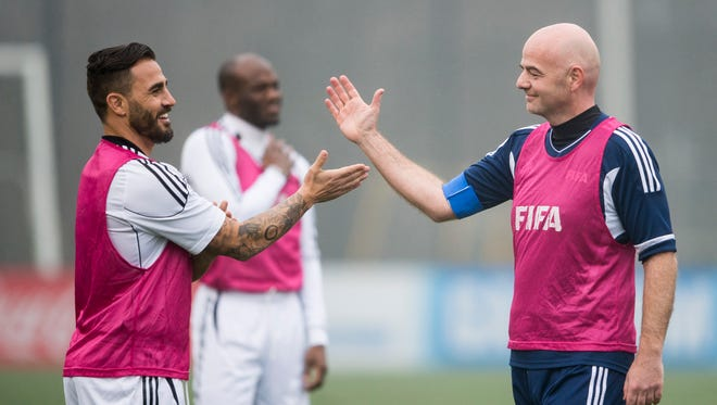 New FIFA President Swiss Gianni Infantino, right, prepares to clap hands with former Italian soccer player Fabio Cannavaro during a friendly soccer match at the home of FIFA in Zurich, Switzerland, Monday, Feb. 29, 2016.