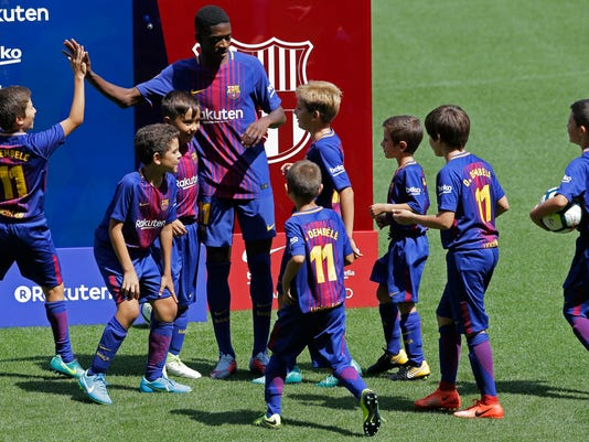 EDS NOTE : SPANISH LAW REQUIRES THAT THE FACES OF MINORS ARE MASKED IN PUBLICATIONS WITHIN SPAIN - FC Barcelona's new player Ousmane Dembele shakes hands with children during his official presentation at the Camp Nou stadium in Barcelona, Spain, Monday, Aug. 28, 2017.  Barcelona is shoring up its attack following Neymar's departure by buying Ousmane Dembele from Borussia Dortmund in a deal that could reach 147 million euros (about US dollars 173 million). (AP Photo/Manu Fernandez)