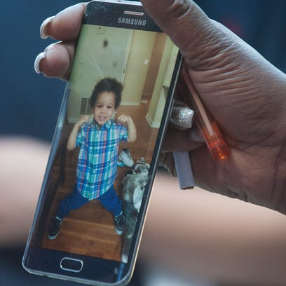 An unidentified family member shows a photo of Jamil