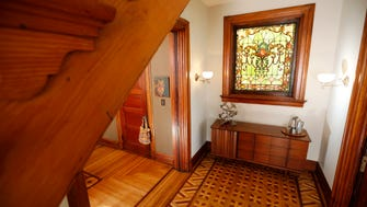 A small foyer featuring unique wood flooring and a leaded window.