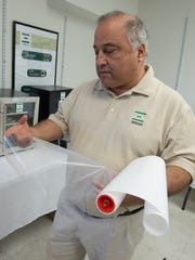 Bamdad Bahar, president of Xergy Inc. in Seaford, examines a roll of the company's Xion Ion Exchange Membranes, which transports dissolved ions across a conductive polymeric membrane often used in desalination and chemical recovery applications.