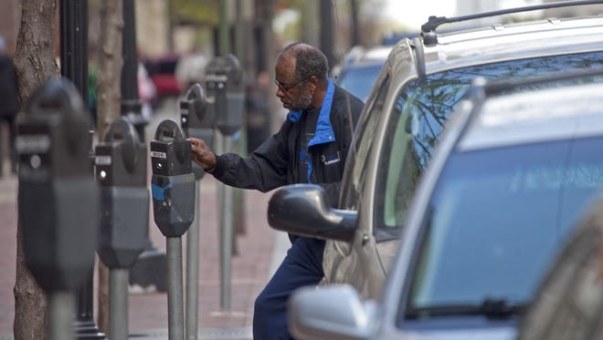 Harold Moore, of New Castle, feeds the parking meter on the 800 block of Market Street Wednesday, April 11,  2012, before having lunch at a local restuarant. The News Journal/JENNIFER CORBETT