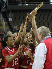 Holmes players hoist the championship trophy after defeating Cooper 58-52 in the Girls' Ninth Region Basketball Tournament championship game at NKU's BB&T Arena, Sunday, March 5, 2017.