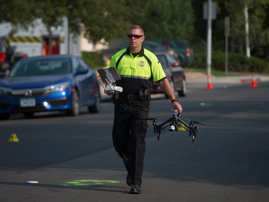 A member of the Fort Collins Police Crash Team prepares to deploy a drone to assist in an investigation at the intersection of Whitcomb and Juniper Streets on Thursday, September 7, 2017. The intersection is expected to be closed for the a few more hours after a CSU police officer was injured when they were dragged by a stolen Chevrolet Blazer.