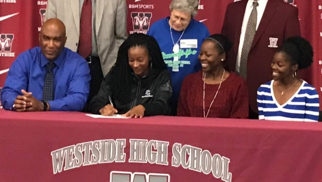 Trinity Wililams, center, signs with Presbyterian College to play volleyball Nov. 8 at Westside High School.