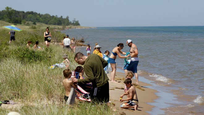 Visitors enjoy the beach at Kohler-Andrae State Park.