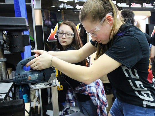 """Hotwire Robotics team members work on the team robot, """"Chaser."""""""