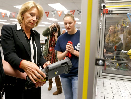 U.S. Secretary of Education Betsy DeVos learns how to use a training robot during a 2017 tour of Oakland High School's Mechatronics program, in Murfreesboro.