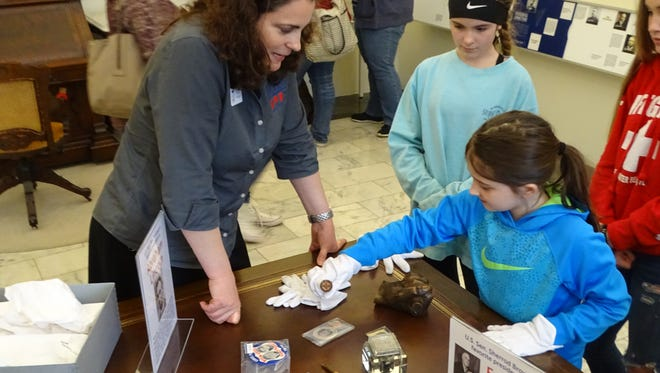 Christie Weininger, executive director of the Rutherford B. Hayes Presidential Library and Museums, talks with Alexis Green, 8, of Sandusky about some of the historical artifacts used by American presidents and preserved at the museum as part of the museum's Presidents Day festivities.
